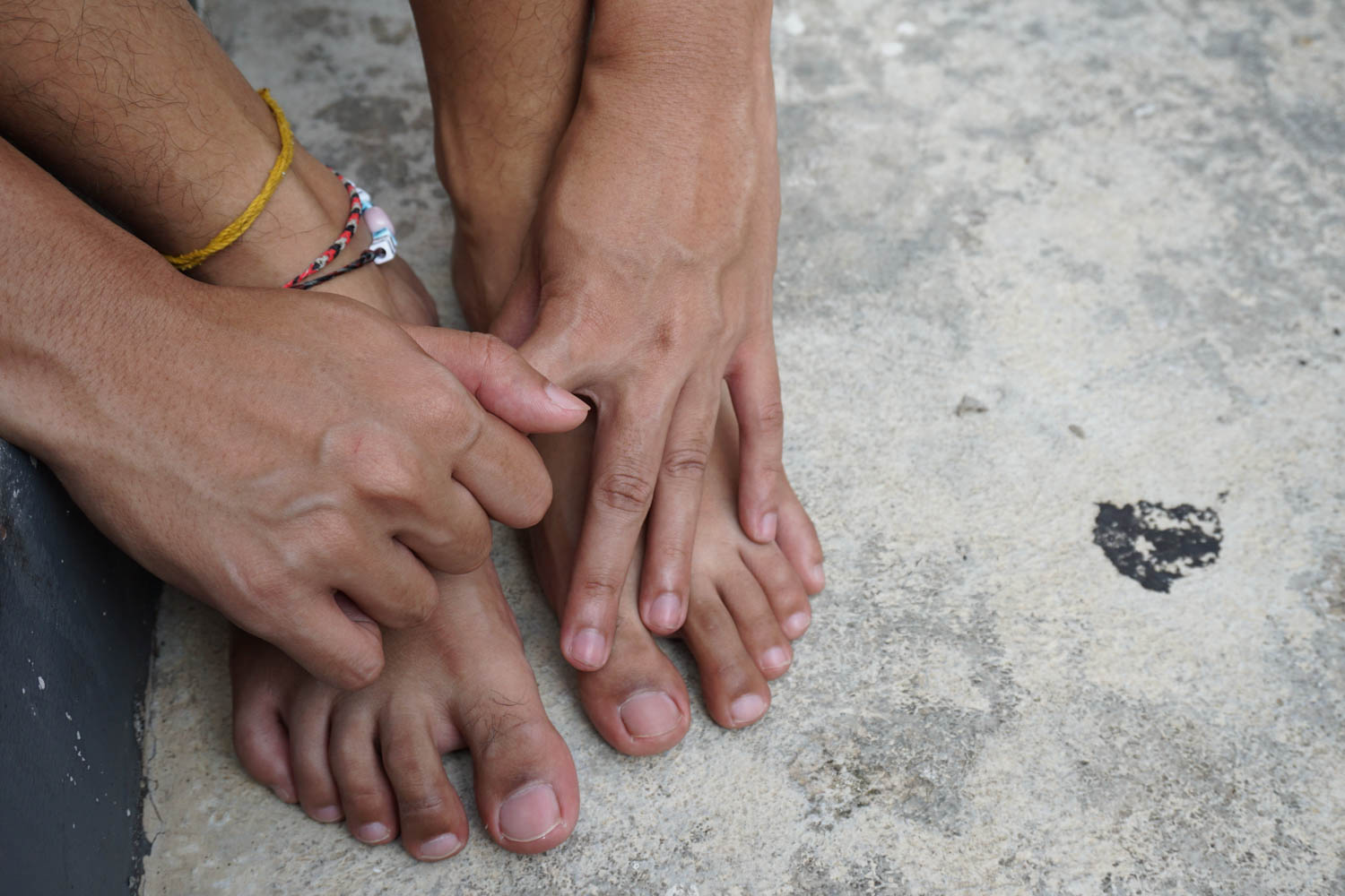 Hand touching feet together