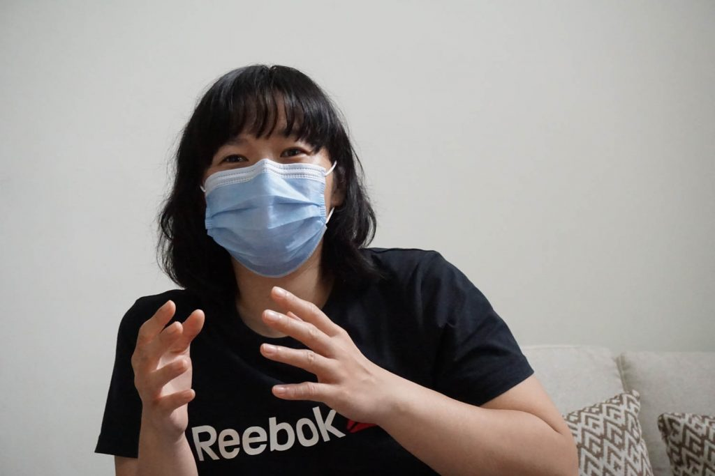 woman wearing a black shirt in a mask speaking