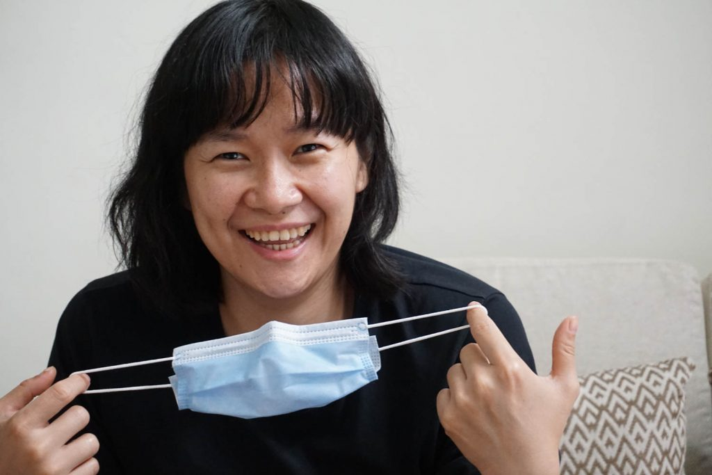woman wearing a black shirt taking off her mask and smiling