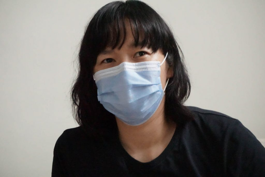 woman wearing black in mask contemplating